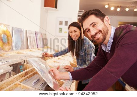 Two people browsing records at a record shop, portrait
