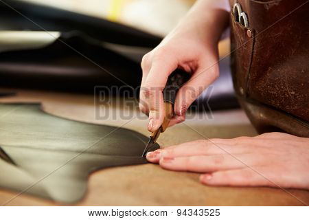 Shoemaker cutting leather in a workshop, close up