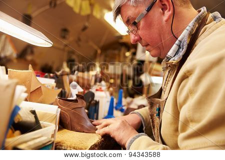 Senior shoemaker working with leather in a workshop, close up