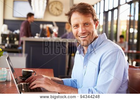 Man working on laptop in a coffee shop
