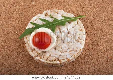 Rice Cracker With Tomato On A Cork Table