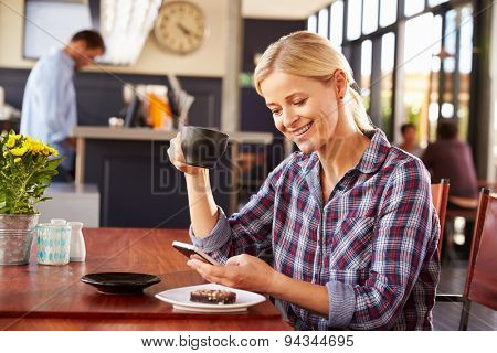 Woman using smart phone at a coffee shop