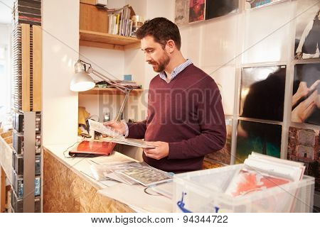 Man working behind the counter at a record shop, portrait