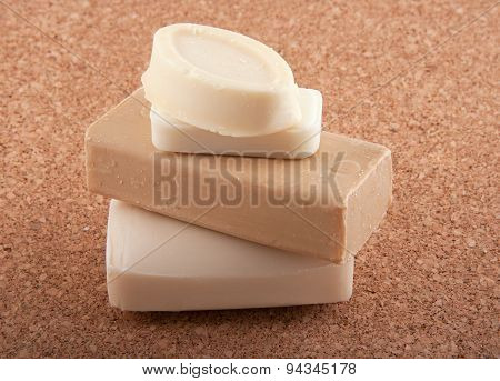 Four Soap Bars On A Cork Bachground