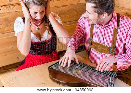 Man playing poorly on zither in mountain hut, his woman in covering her ears with hands