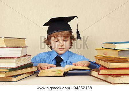 Little serious boy in academic hat reading old books