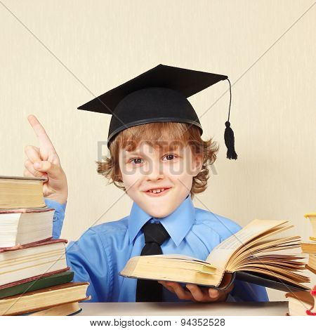Little smiling boy in academic hat quoted old book