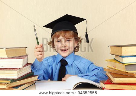 Little smiling boy in academic hat with rarity pen among old books