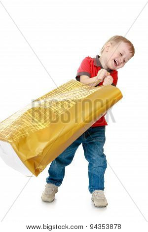 small child waving a large paper bag for shopping