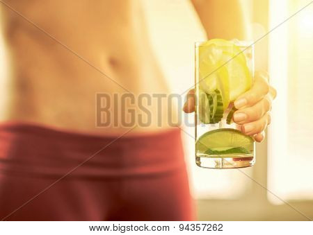 Healthy coctail in the hands of fitness female.