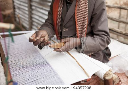 Hands of a man making cloth on a traditional loom in Africa