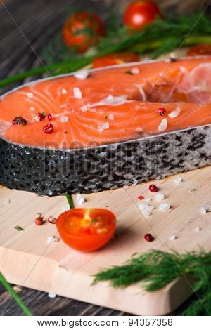 Fresh raw salmon steak on wooden cutting board with salt, tomatoes and herbs