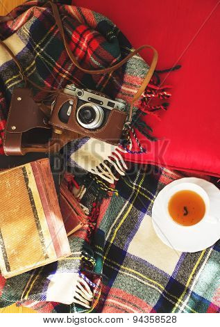Composition with cup of tea vintage camera old books on sofa with plaid. Toned. Top view.