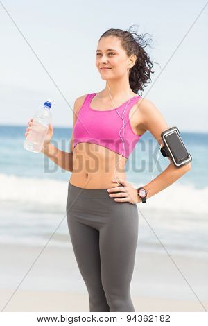 Pretty woman holding water bottle at the beach