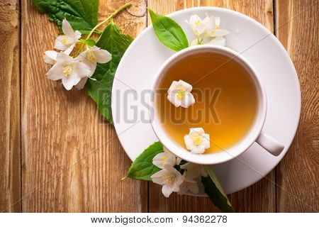 Herbal tea with jasmine flowers on wooden background
