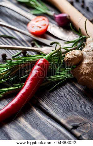 Spices. Chili pepper, ginger and rosemary over wooden background.