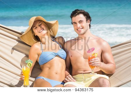 Happy couple relaxing on the hammock at the beach