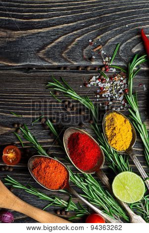 Spices. Herbs and spices selection in old metal spoons over wooden background. Rosemary, salt and lime.