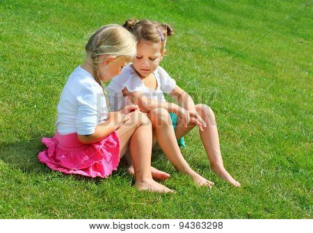 Two little girls sitting and talking on grass. Happy holidays concept.