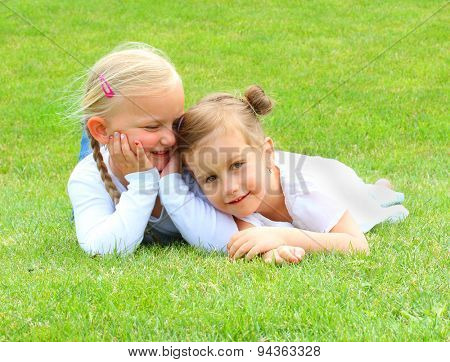 Two little girls lying on grass. Happy holidays concept.