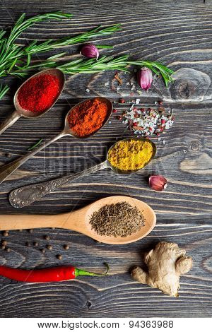 Spices. Herbs and spices selection in old metal spoons over wooden background. Rosemary, ginger and chili pepper.