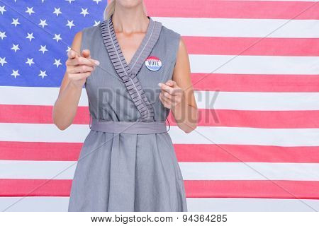 Blonde woman gesturing in front of american flag with badge on white background