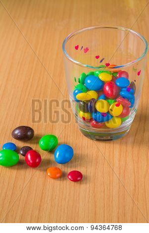 Colorful chocolate and milk into a glass placed on a wooden floor.
