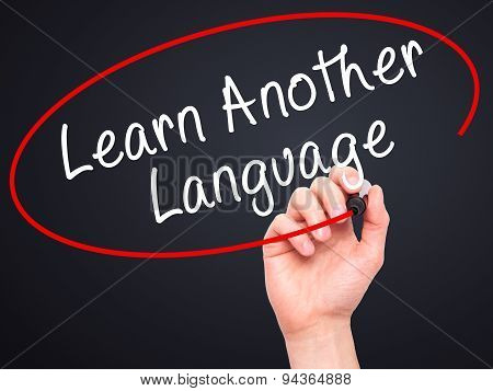 Man Hand writing Learn Another Language with black marker on visual screen.