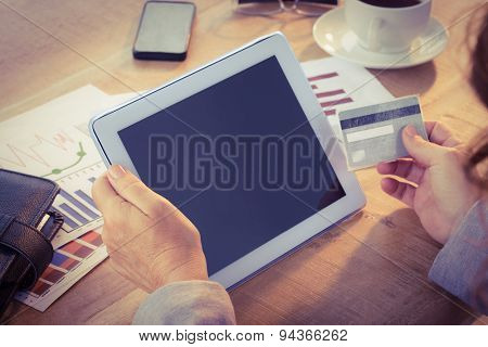 Businesswoman using credit card on a tablet in the office