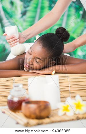 Pretty woman enjoying a herbal compress massage at the health spa