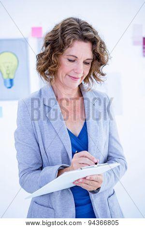 Creative businesswoman taking note on clipboard in office