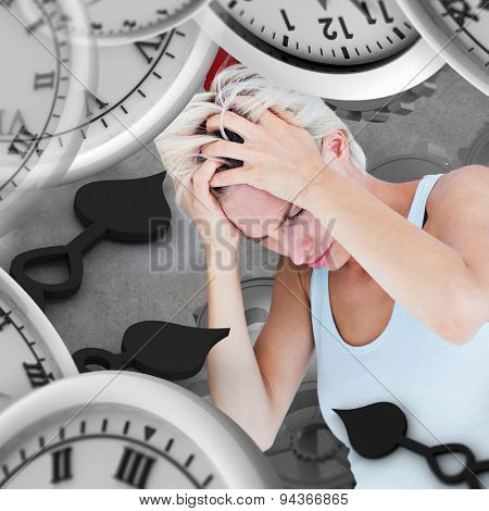 Sad blonde woman with head pain holding her head against grey background