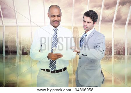 Businessmen working together against room with large window looking on city