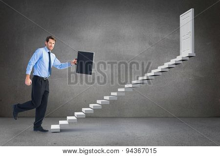 Walking and smiling businessman with suitcase against grey room