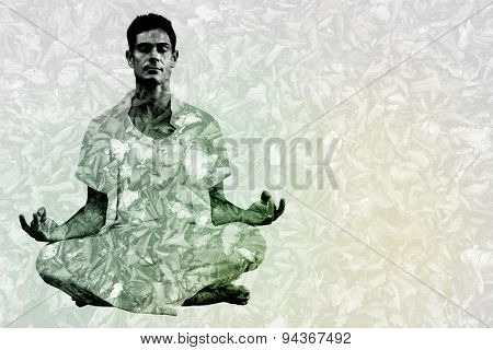 Handsome man in white meditating in lotus pose against detail shot of dry leaves