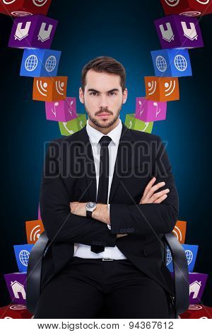 Serious businessman sitting with arms crossed against blue background with vignette