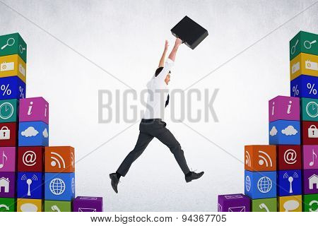 Businessman leaping with his briefcase against grey room