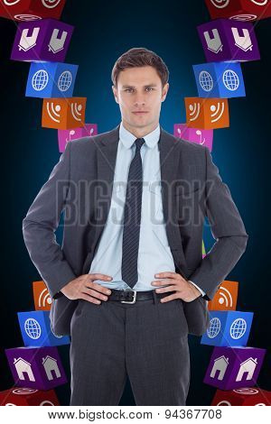 Serious businessman with hands on hips against blue background with vignette