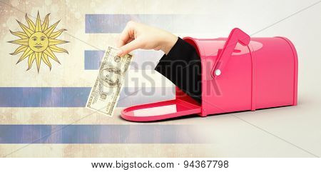 Businesswomans hand holding hundred dollar bill against uruguay flag in grunge effect