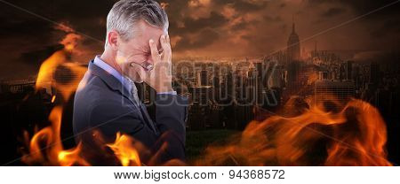 Businessman with headache against stormy sky over city