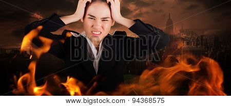 Stressed businesswoman with hands on her head against stormy sky over city