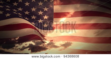 Digitally generated united states national flag against blue and orange sky with clouds