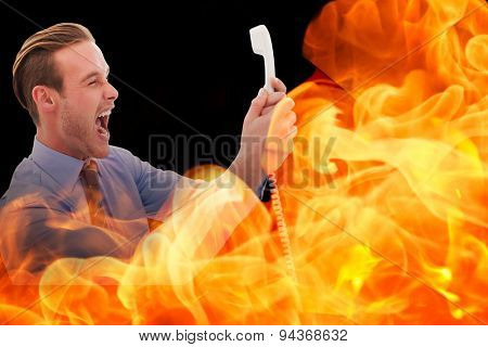 Businessman shouting at phone against black