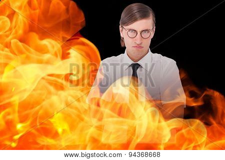 Geeky businessman looking at camera with arms crossed against black