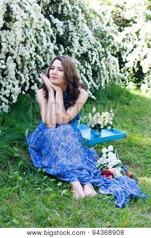 The Girl In A Blue Dress Sitting On The Grass Among Flowers Grains