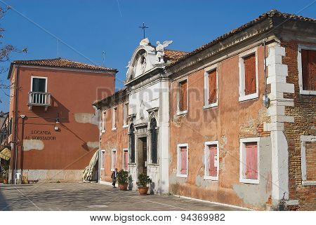 Exterior of the old abandoned building with decaying facade in Murano, Italy.