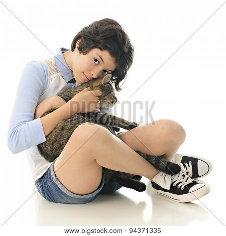 An attractive young teen snuggling with her pet kitty.  On a white background.