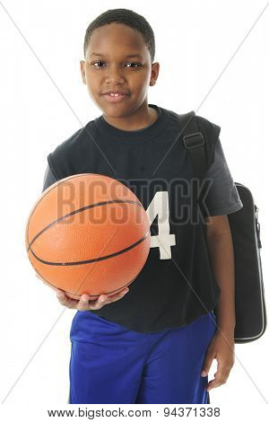 A preteen athlete carrying his gym bag while holding out his basketball in an invitation to play.  On a white background.