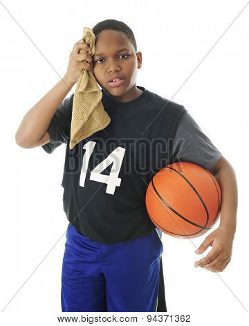 A preteen basketball player hot and tired after a  rough game.  He's wiping his brow with a towel while carrying the basketball under his arm.  On a white background.