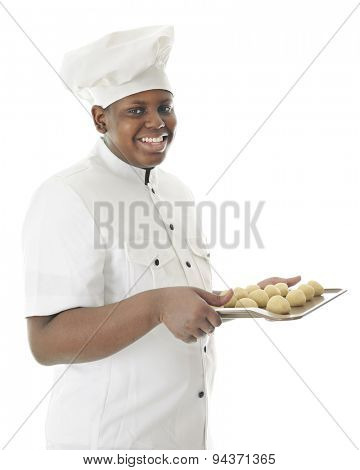 A young chef happily looking at the viewer as he carries a cookie sheet filled with a dozen balls of dough.  On a white background.